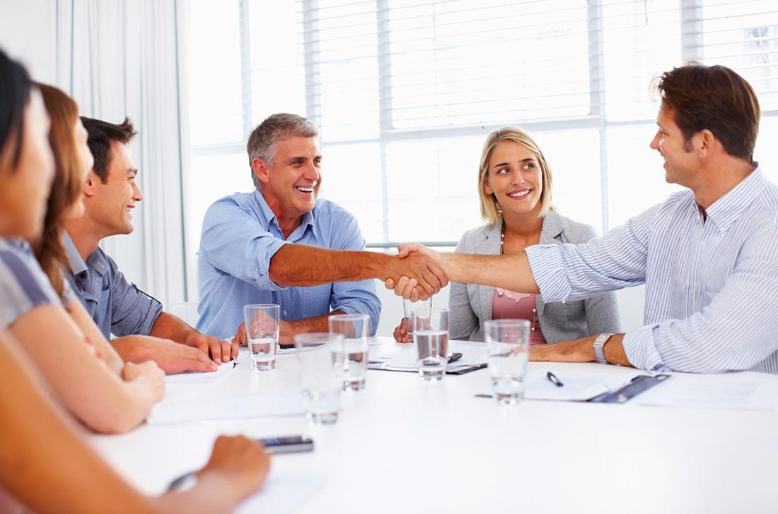 Chef und neuer Mitarbeiter besiegeln per handschlag den Arbeitsvertrag.